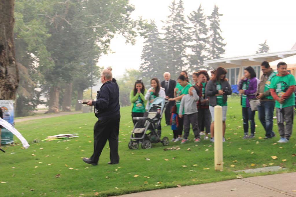 Fr. Larry Pederson sprinkling holy water with Mayor Norman Mayer at the background